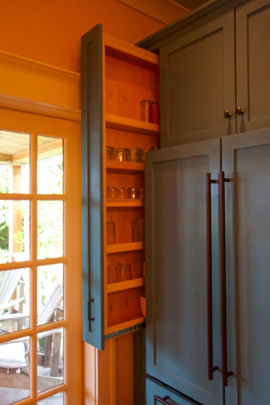 Narrow pantry cabinet left of refrigerator.