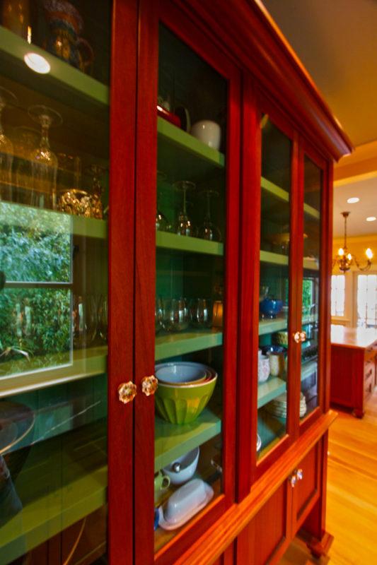 Mahogany dish pantry with painted vintage green interior.